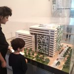 Kind steht vor Modell des neuen Check Point Buildings